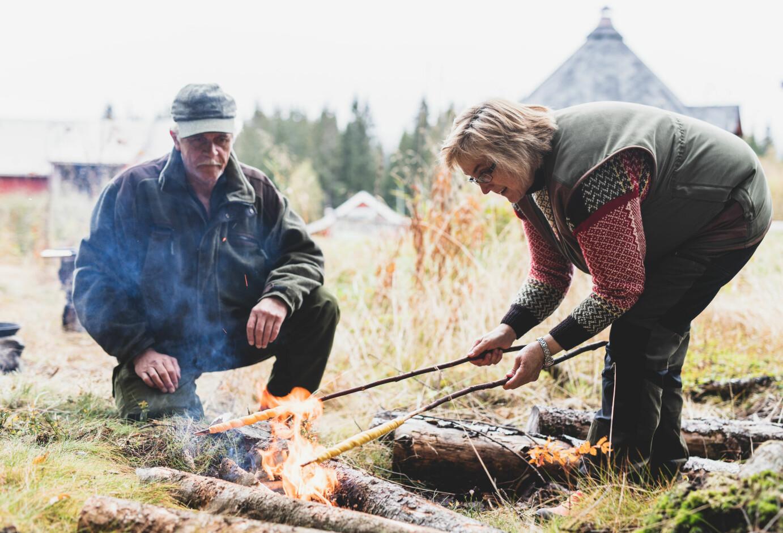 BAKST MED SMAK: Ekteparet Arne Nohr og Kirsten Winge er oppvokst med bålmat. Til steking av førjulsbaksten anbefaler de å bygge et jegerbål eller et tosteinsbål . Over disse bålene står steikepanna støtt under steikingen.